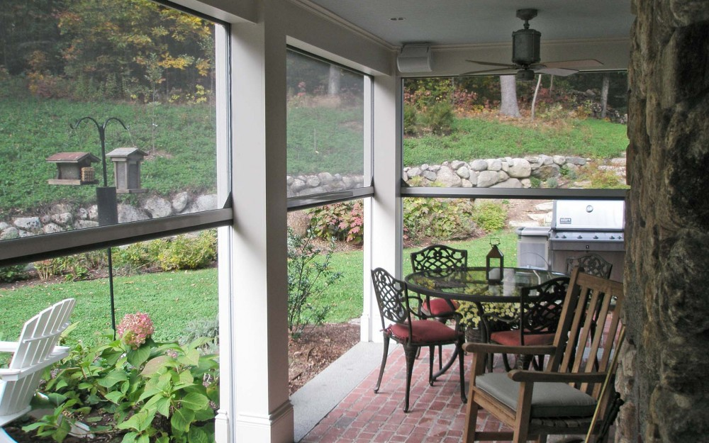 Caustic New England home with screened in patio by Phantom Screens
